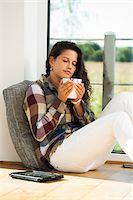 Teenage girl sitting on floor next to window, holding cup, Germany Stock Photo - Premium Royalty-Freenull, Code: 600-07148153