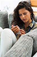 Teenage girl sitting on sofa looking at smart phone, Germany Stock Photo - Premium Royalty-Freenull, Code: 600-07148156