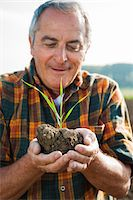 Close-up portrait of farmer standing in field, holding seedling plant from crop, Germany Stock Photo - Premium Royalty-Freenull, Code: 600-07148337