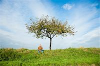 single fruits tree - Farmer sitting on hill next to apple tree, eating apple, Germany Stock Photo - Premium Royalty-Freenull, Code: 600-07148342