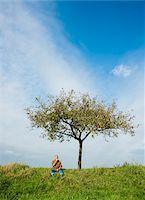 single fruits tree - Farmer sitting on hill next to apple tree, eating apple, Germany Stock Photo - Premium Royalty-Freenull, Code: 600-07148343