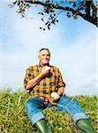 Portrait of farmer sitting in field eating apple, Germany Stock Photo - Premium Royalty-Free, Artist: Uwe Umstätter, Code: 600-07148344