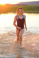 Girl running in the shallow water of a lake Stock Photo - Premium Rights-Managednull, Code: 853-07148642