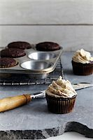 slate - Frosting freshly made cupcakes, studio shot Stock Photo - Premium Royalty-Freenull, Code: 600-07156146