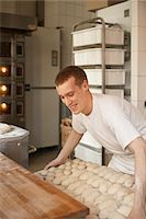 Male baker lifting tray of bread dough lumps in bakery, Le Boulanger des Invalides, Paris, France Stock Photo - Premium Rights-Managednull, Code: 700-07156251
