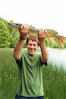 Smiling teenage boy with caught fish Stock Photo - Premium Royalty-Free, Artist: Science Faction, Code: 6102-07158165