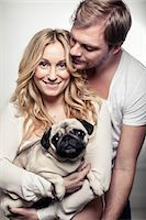 Portrait of happy pregnant woman holding pug dog with man embracing h