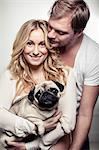 Portrait of happy pregnant woman holding pug dog with man embracing her from behind Stock Photo - Premium Royalty-Free, Artist: Minden Pictures, Code: 698-07158435