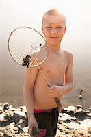Shirtless boy holding badminton racket on beach Stock Photo - Premium Royalty-Freenull, Code: 698-07158479