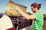 Man checking oil in propeller aeroplane