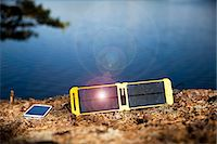 solar power - Solar charger and smart phone on lakeshore Stock Photo - Premium Royalty-Freenull, Code: 698-07158519