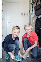 Portrait of smiling boys tying shoe laces on floor Stock Photo - Premium Royalty-Freenull, Code: 698-07158533