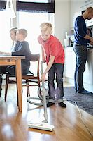 Boy vacuuming hardwood floor with family in background Stock Photo - Premium Royalty-Freenull, Code: 698-07158554