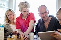 Man and sons using digital tablet while mother reading newspaper at dining table Stock Photo - Premium Royalty-Freenull, Code: 698-07158558