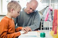 Father helping son with homework at table Stock Photo - Premium Royalty-Freenull, Code: 698-07158561