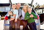 Portrait of happy family sitting on car's trunk S