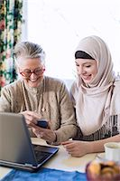 Senior woman with female home caregiver visiting bank through laptop at home Stock Photo - Premium Royalty-Freenull, Code: 698-07158586