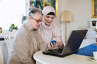 Young female home caregiver with senior woman entering bank using laptop at home Stock Photo - Premium Royalty-Freenull, Code: 698-07158587