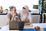 Happy young female home caregiver with senior woman doing bank transaction on laptop Stock Photo - Premium Royalty-Free, Artist: Blend Images, Code: 698-07158588
