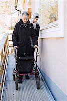 Female home caregiver helping senior woman with walking frame through passage Stock Photo - Premium Royalty-Freenull, Code: 698-07158609
