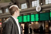 Businessman looking at arrival departure board on railway station Stock Photo - Premium Royalty-Freenull, Code: 698-07158652