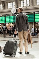 Businessman with luggage standing on railway station Stock Photo - Premium Royalty-Freenull, Code: 698-07158653