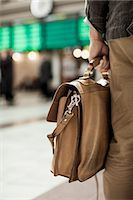 Midsection of businessman carrying bag while standing on railway station Stock Photo - Premium Royalty-Freenull, Code: 698-07158656