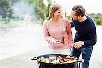 Happy couple looking at each other while barbecuing on pier Stock Photo - Premium Royalty-Freenull, Code: 698-07158687