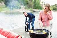 dog in heat - Happy woman using mobile phone while barbecuing with man and dog in background on pier Stock Photo - Premium Royalty-Freenull, Code: 698-07158688