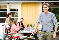 Portrait of happy man barbecuing with friends at dining table in background Stock Photo - Premium Royalty-Freenull, Code: 698-07158691