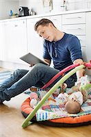 Father using digital tablet and mobile phone while baby sleeping on mat in kitchen Stock Photo - Premium Royalty-Freenull, Code: 698-07158707