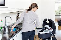 Rear view of woman looking at baby girl in carriage while washing utensils in kitchen Stock Photo - Premium Royalty-Freenull, Code: 698-07158712