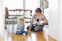 Mother cleaning floor with daughter while holding baby at home Stock Photo - Premium Royalty-Freenull, Code: 698-07158726
