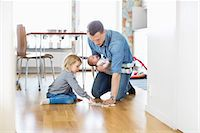 Father cleaning floor with daughter while holding baby girl at home Stock Photo - Premium Royalty-Freenull, Code: 698-07158727