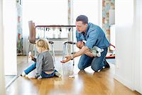 Father holding baby girl while cleaning floor with daughter at home Stock Photo - Premium Royalty-Freenull, Code: 698-07158728
