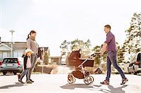 Side view of parents with baby carriage and daughter walking on street Stock Photo - Premium Royalty-Freenull, Code: 698-07158737