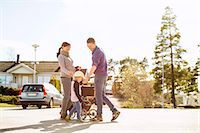 Parents with baby carriage and daughter on street Stock Photo - Premium Royalty-Freenull, Code: 698-07158738
