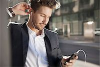 Young businessman listening music through mobile phone outdoors Stock Photo - Premium Royalty-Freenull, Code: 698-07158773