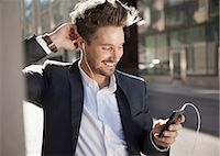 Young businessman smiling while listening music through mobile phone on street Stock Photo - Premium Royalty-Freenull, Code: 698-07158774