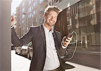 Happy young businessman listening music through mobile phone on street Stock Photo - Premium Royalty-Freenull, Code: 698-07158775