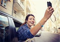Happy businesswoman photographing through mobile phone from car window on street Stock Photo - Premium Royalty-Freenull, Code: 698-07158788