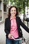 Portrait of happy businesswoman with bicycle standing on sidewalk Stock Photo - Premium Royalty-Freenull, Code: 698-07158807