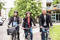 Happy business people riding bicycles on street Stock Photo - Premium Royalty-Freenull, Code: 698-07158813