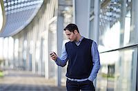 Businessman using cell phone outdoors Stock Photo - Premium Royalty-Freenull, Code: 6113-07159107