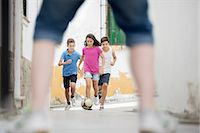 female playing soccer - Children playing with soccer ball in alley Stock Photo - Premium Royalty-Freenull, Code: 6113-07159156