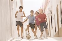 preteen girl - Children playing with soccer ball in alley Stock Photo - Premium Royalty-Freenull, Code: 6113-07159162