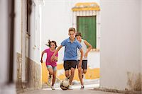 female playing soccer - Children playing with soccer ball in alley Stock Photo - Premium Royalty-Freenull, Code: 6113-07159172