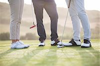 Friends standing on golf course Stock Photo - Premium Royalty-Freenull, Code: 6113-07159203