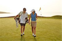 Golfer and caddy walking on golf course Stock Photo - Premium Royalty-Freenull, Code: 6113-07159306