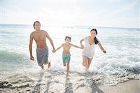 preteen boy shirtless - Family running in surf on beach Stock Photo - Premium Royalty-Freenull, Code: 6113-07159486